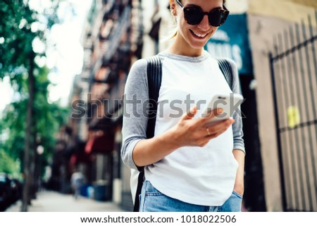 Cropped view of cheerful hipster girl read chat on mobile phone satisfied with good internet walking on street, smiling female traveler strolling in town using navigation on smartphone checking route #1018022506