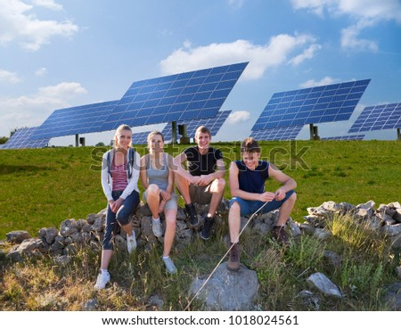 People sitting on wall by solar panels #1018024561