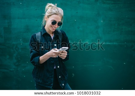 Smiling caucasian young woman sending message on smartphone standing near promotional copy space background, positive trendy hipster girl blogging in social network using mobile phone with internet Royalty-Free Stock Photo #1018031032