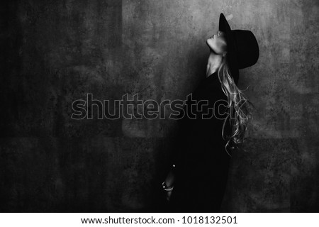 Beautiful young mysterious blond girl in black hat and black jacket on gray background. Eyes are covered with a hat. Manicure - long red nails, nail polish. Fashion, beauty. #1018132501