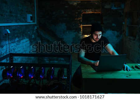 Shot of a young man working on a computer next to a cryptocoin mine #1018171627