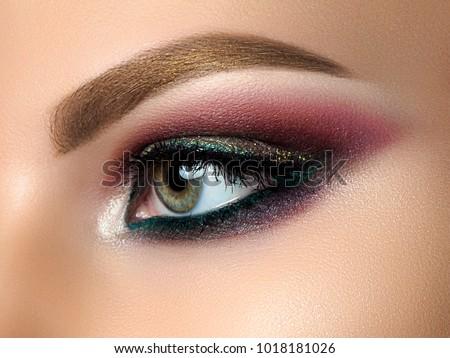 Close up of beautiful woman eye with multicolored smokey eyes makeup. Modern fashion make up. Studio shot