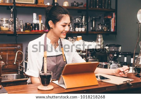 Barista woman using digital tablet compute in coffee shop counter bar #1018218268