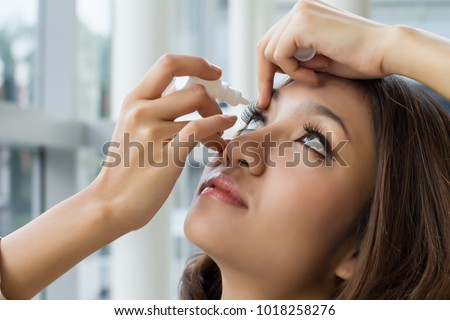 woman using eye drop, woman dropping eye lubricant to treat dry eye or allergy; sick asian girl treating eyeball irritation or inflammation; sick woman suffering from irritated eye, optical symptoms #1018258276