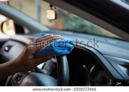 Close up of human hand are cleaning in a car. #1018272466