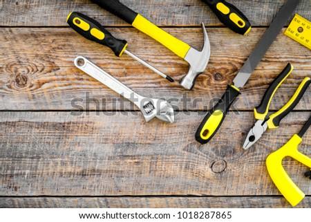 Repair tool kit. File, hummer, corner ruler on rustic wooden background top view pattern copy space #1018287865