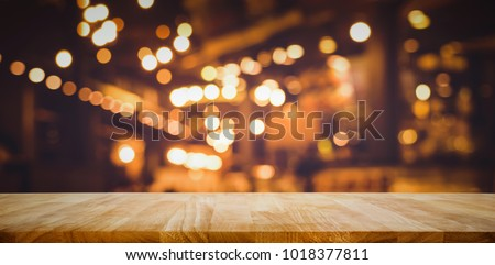 Wood table top (Bar) with blur light bokeh in dark night cafe,restaurant background .Lifestyle and celebration concepts ideas Royalty-Free Stock Photo #1018377811