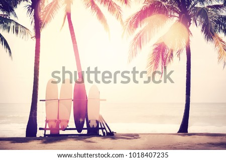 Surfboard and palm tree on beach double exposure with colorful bokeh sun light texture abstract background. Summer vacation and sport extreme concept. Vintage tone filter color style. Royalty-Free Stock Photo #1018407235