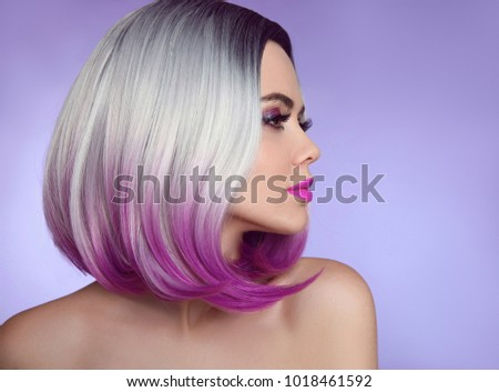 Colorful dyed Ombre hair extensions. Fashion haircut. Beauty Model Girl blonde with short bob purple hairstyle isolated on purple background. Closeup woman portrait. #1018461592