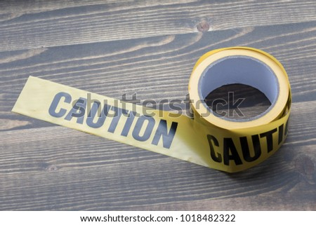 yellow caution tape on a wooden background. Safety Barrier For Police Barricade, For Contractors Royalty-Free Stock Photo #1018482322