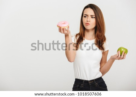Portrait of a confused young woman choosing between donut and green apple isolated over white background #1018507606