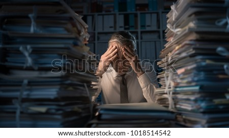 Desperate businessman working in the office late at night and overloaded with work, his desktop is covered with paperwork: business management and deadlines concept #1018514542