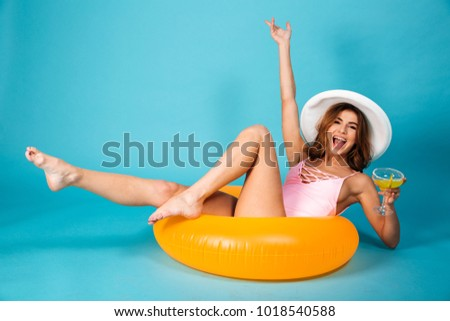 Image of a happy excited girl dressed in swimsuit sitting on inflatable ring and holding cocktail isolated over blue background
