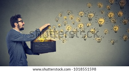 Side view of happy man holding a box with brilliant ideas being creative and smiling Royalty-Free Stock Photo #1018551598