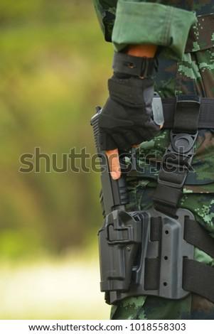 The military unit carries a short gun #1018558303