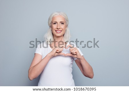 Perfect, nice, aged, old, pretty woman, lover in t-shirt making, showing heart figure with fingers, looking at camera, celebrating woman's day, standing over gray background #1018670395