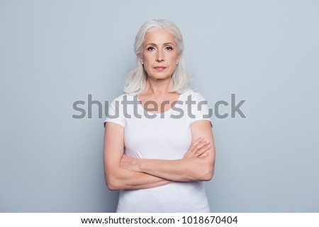 Portrait  of nice, charming, aged, perfect, nice, pretty, concentrated, woman with folded hands, serious expression, looking at camera,  standing over gray background #1018670404