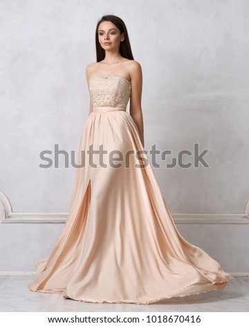 Full body portrait of gorgeous young brunette woman dressed in exquisite nude ball gown with lace top. Attractive female model in elegant strapless dress posing against white wall on background. #1018670416