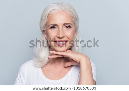 Charming old woman holding hand under chin with beaming smile looking at camera over gray background #1018670533