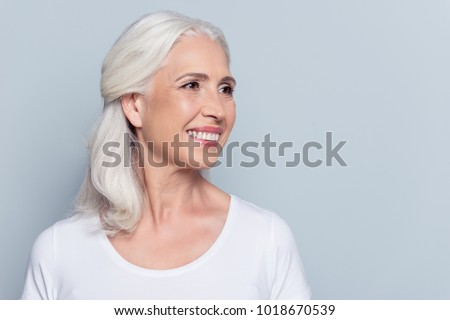 Close up portrait with copy space of half turned attractive, nice, smiling, perfect, pretty woman looking to the side over gray background #1018670539