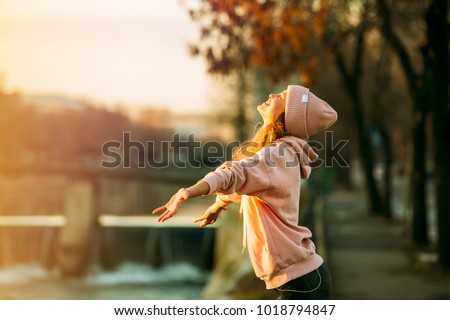 cool hipster young girl in pink hoodie standing by a river in the city very happy smiling to the sun and enjoying it, on autum or springtime #1018794847