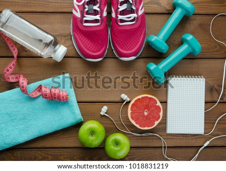 Fitness concept with sneakers dumbbells bottle of water apple pomelo and measure tape on wooden table background  #1018831219