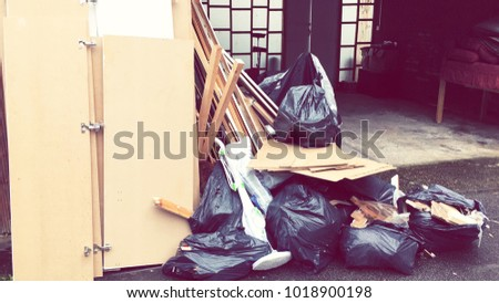 Garage Clearance. Old Sofa And Dismantled Cupboard Parts Lean Against The Wall And In Black Garbage Bags. Mitcham, England. Royalty-Free Stock Photo #1018900198