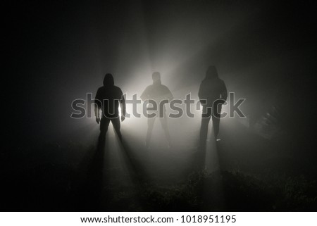 three men's silhouettes in the fog are illuminated by the light of the headlights behind #1018951195