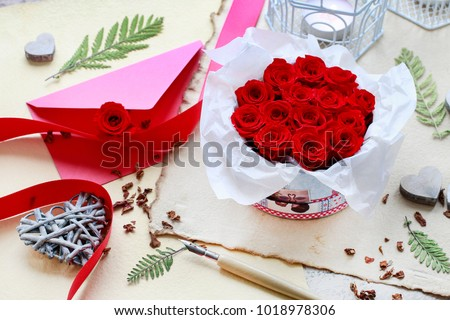 Valentine's Day decorations: box with red roses, vintage paper for greetings, wooden and wicker hearts. #1018978306