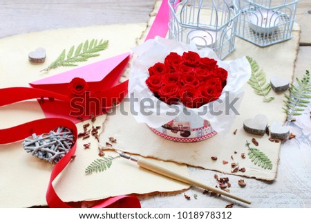 Valentine's Day decorations: box with red roses, vintage paper for greetings, wooden and wicker hearts. #1018978312