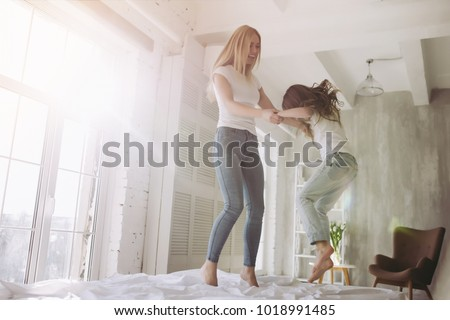 Attractive young woman and her little cute daughter are having fun in bed while being at home together. Happy Mother's Day! #1018991485
