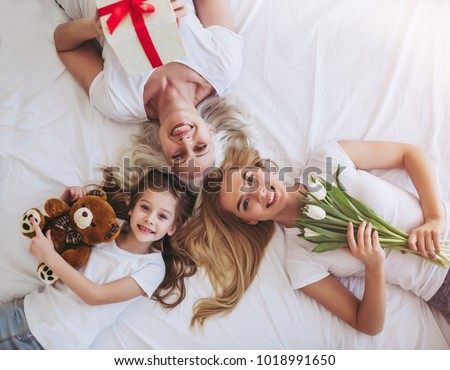 Top view of little girl, her attractive young mother and charming grandmother are lying on bed while spending time together at home. Women's generation. International Women's Day. Happy Mother's Day. #1018991650