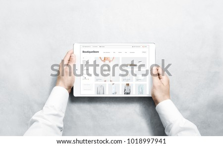 Hands holding tablet with fashion webstore mock up on screen, isolated. Clothing web page interface mockup. Internet website online template on the device display. Royalty-Free Stock Photo #1018997941
