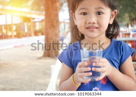 Portrait of asian kid drinking glass of water  #1019063344