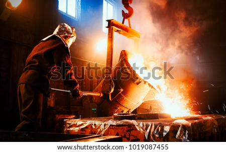 Workers operates at the metallurgical plant. The liquid metal is poured into molds. Worker controlling metal melting in furnaces. Royalty-Free Stock Photo #1019087455