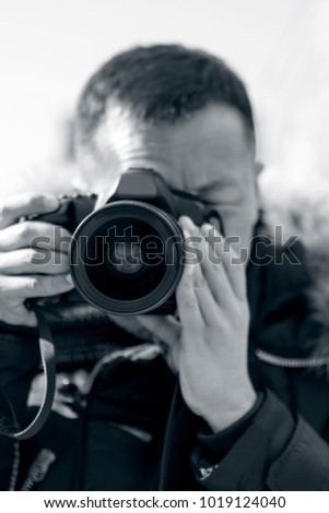 A male photographer takes a camera with a camera #1019124040