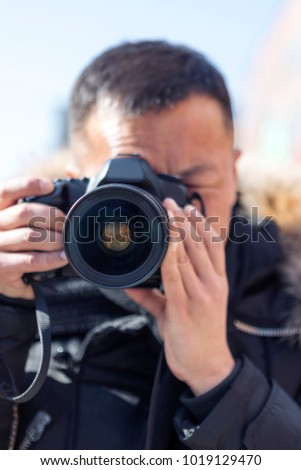 A male photographer takes a camera with a camera #1019129470