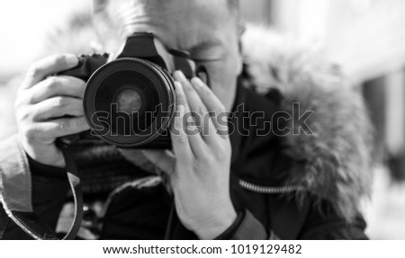 A male photographer takes a camera with a camera #1019129482
