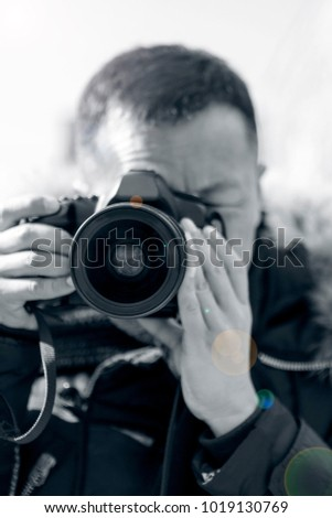 A male photographer takes a camera with a camera #1019130769