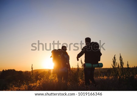 Silhouettes of two hikers with backpacks walking at sunset. Trekking and enjoying the sunset view #1019166346