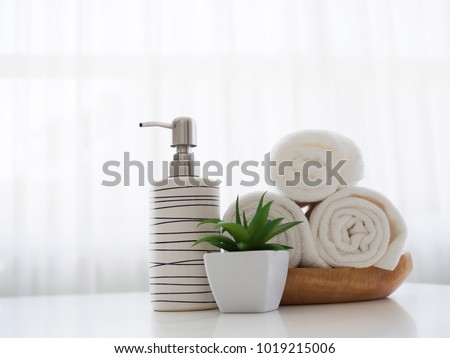 Perfume bottle and towels studio shot on white table #1019215006