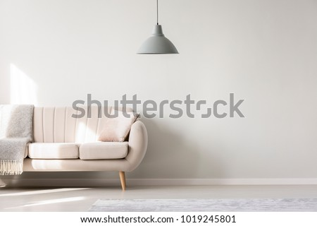 Beige sofa against white, empty wall with copy space in simple living room interior with lamp #1019245801