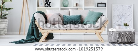 Pouf next to beige sofa with green cushions in apartment interior with map poster #1019251579