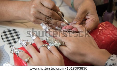 manicurist removing cuticle from persons nail #1019393830