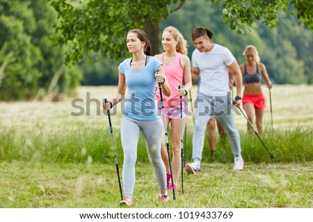Group in the nature nordic walking in their leisure time #1019433769