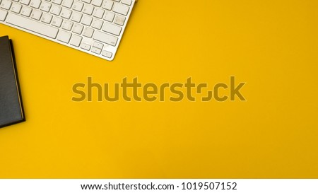 workspace desk with keyboard and notebook copy space background yellow #1019507152