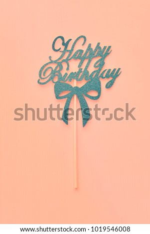 "Image at center of blue paper gritter cut the word""Happy Birthday""with pink plastic sticks for holding or embroidering on pink background,birthday tag."