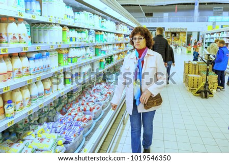 Russia, Samara, May 17, 2016: a mature curly woman standing in the department of dairy products in a large supermarket. Text in Russian: a bread court. #1019546350
