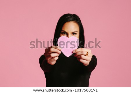 Woman in black showing pink heart covering half her face, be my valentine #1019588191