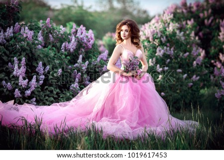 A young beautiful girl in a pink dress is walking in a blooming lilac garden #1019617453